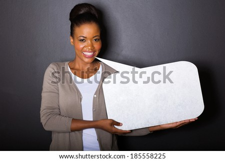 pretty african woman with blank text bubble on black background - stock photo