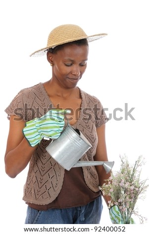 Pretty African woman with watering can and flowers - stock photo