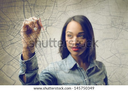 pretty african woman writing on the map - stock photo