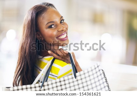 pretty african young lady shopping in mall - stock photo