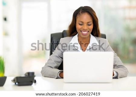 pretty afro american businesswoman using laptop computer - stock photo