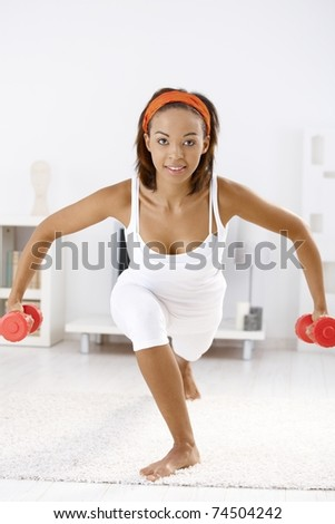 Pretty afro woman exercising with dumbbells, bending on carpet at home.? - stock photo