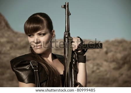 pretty aggressive girl in black clothes with a gun against a background of rocks