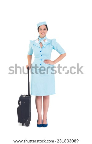 Pretty air hostess holding suitcase on white background - stock photo