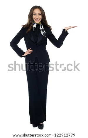 Pretty air hostess presenting copy space with open palm, full length studio shot. - stock photo