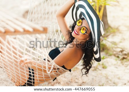 Pretty amazing cheerful young girl on the beach, lying in a hammock and smiling in a black sexy bikini in a wide luxurious hat and mirrored sunglasses are reflected palm trees, lifestyle, tanned  - stock photo