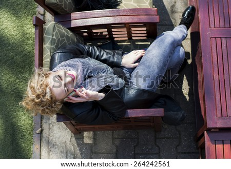 Pretty and attractive young woman with blond curly hair talking on the phone sitting in a cafe.She is smiling as she is communicating with her friends. - stock photo