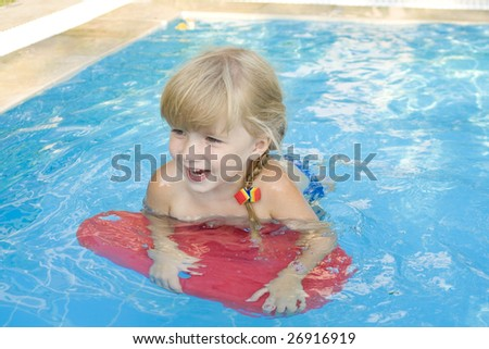Pretty and cheerful little girl   swim in the swimming-pool - stock photo