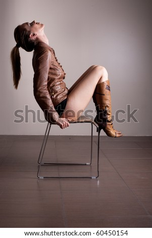 Pretty and sexy woman posing on chair with her head up