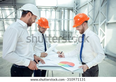 Pretty architects are discussing the plan of constructing. The man is drawing sketches on the blueprint and smiling. His colleagues are looking at it with joy - stock photo