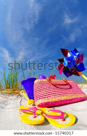 Pretty array of beach accessories on sand dune under blue sky - stock photo