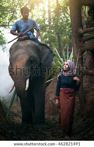 Pretty asia girl standing front of the elephant andYoung man riding on the back of an elephant.