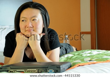 Pretty Asian business woman laying down in hotel room - thinking