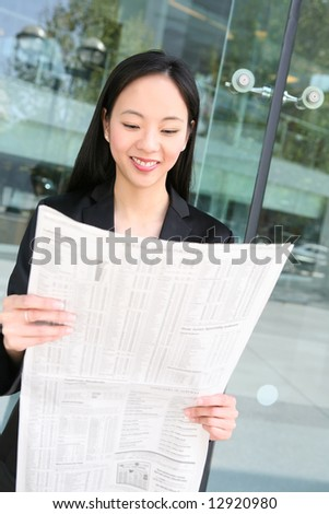 Pretty asian business woman reading the newspaper outside office building
