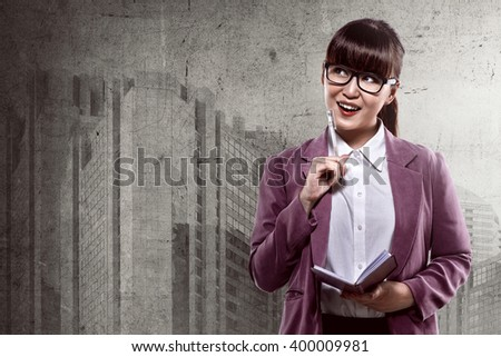 Pretty asian business woman thinking while holding pen and notes - stock photo