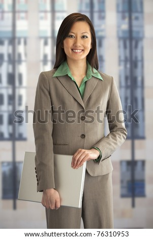 Pretty Asian businesswoman holding a laptop computer - stock photo