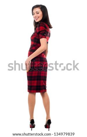 Pretty asian female model looking over her shoulder, full length portrait. - stock photo