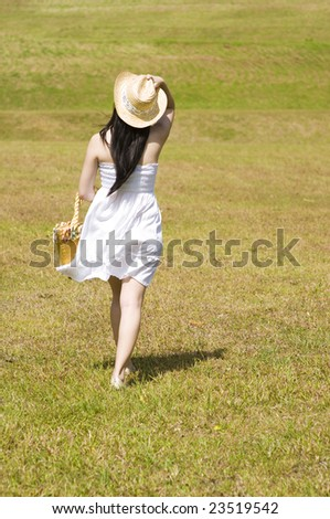 pretty asian female walking away after picnic - stock photo
