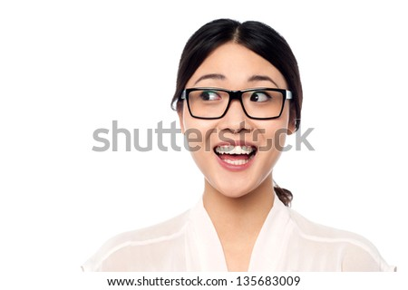 Pretty asian girl looking away in excitement, wearing spectacles.
