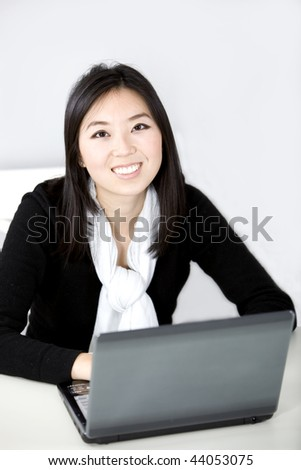 Pretty Asian graduate student using laptop