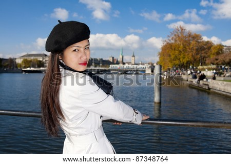 pretty asian in zurich, with the lake, a tram and two famous churches in the background - stock photo