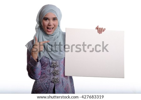 Pretty asian muslim woman wearing traditional malay costume known as songket is smiling while holding a white plain board on white background  - stock photo