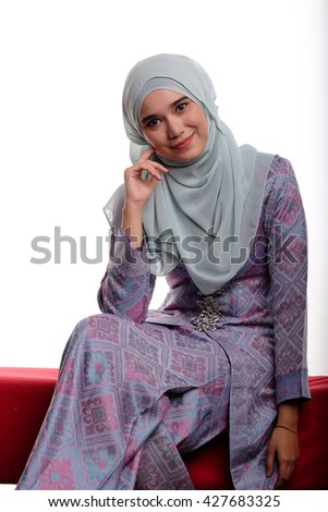 Pretty asian muslim woman wearing traditional malay costume known as songket is smiling while sitting on red sofa on white background  - stock photo