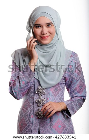 Pretty asian muslim woman wearing traditional malay costume known as songket is smiling while talking on her mobile phone on white background  - stock photo
