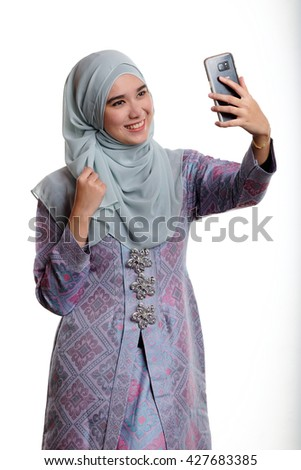 Pretty asian muslim woman wearing traditional malay costume known as songket is taking selfie or self portrait with her mobile phone on white background