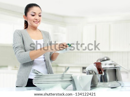 pretty asian woman doing house work, washing dishes - stock photo