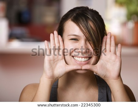 Pretty Asian Woman Framing Face with her Hands - stock photo