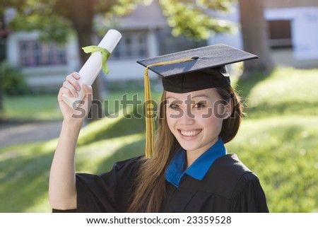 Pretty Asian woman graduate wearing cap and gown holding diploma - stock photo
