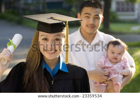 Pretty Asian woman graduating standing with husband and baby - stock photo