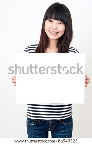 pretty asian woman holding a blank whiteboard - stock photo