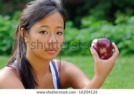 Pretty Asian woman holding apple with bite mark