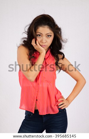 Pretty Asian woman in pink blouse and jeans, standing with a thoughtful expression and her hands in her hair - stock photo