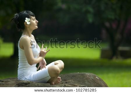 Pretty Asian woman in yoga position. Shot outdoor in a garden - stock photo