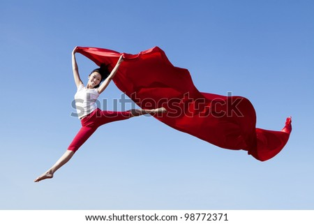 Pretty Asian Woman jumping with scarf shot against blue sky - stock photo
