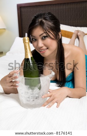 Pretty Asian woman on bed with wine glass and Champagne bucket