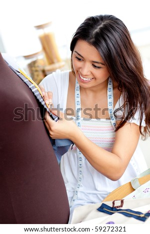 Pretty asian woman sewing clothes in the kitchen at home - stock photo