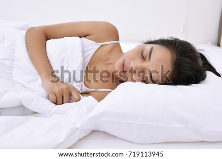 Pretty asian woman sleeping and hugging blanket in the bed