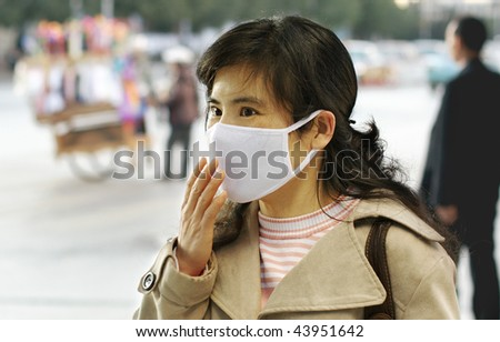 pretty asian woman wearing a face mask - stock photo