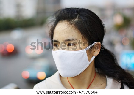 Pretty Asian woman wearing a face mask to protect against pollution or disease. - stock photo