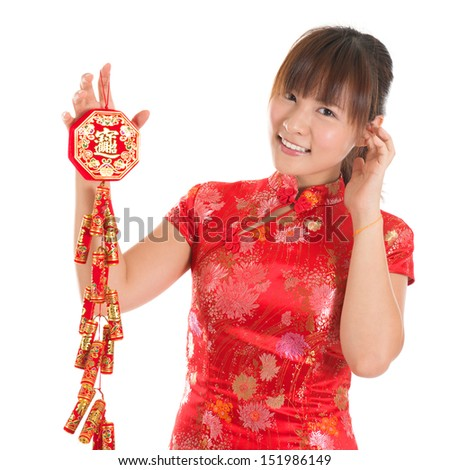 Pretty Asian woman with Chinese traditional dress cheongsam or qipao holding fire crackers. Chinese new year concept, the Chinese words means prosperity. - stock photo