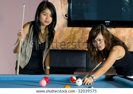 pretty asian women playing pool. focus on the one who is playing. - stock photo
