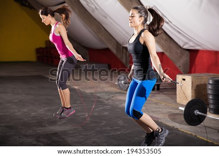 Pretty athletic girls using jump ropes for her workout in a gym - stock photo
