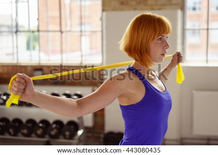 Pretty athletic woman with short red hair uses yellow stretch band while exercising in a fitness center