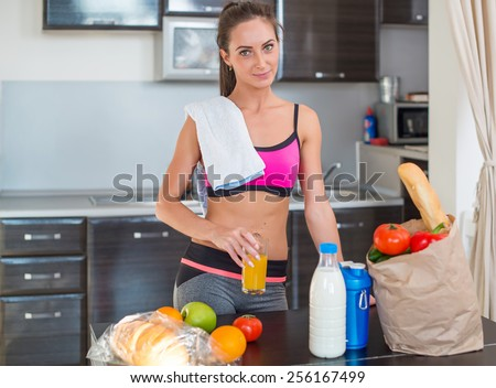 Pretty attractive athletic sportive lady woman standing in kitchen with a towel on her shoulder and healthy food fresh fruits milk bread around drinking cold drink beverage. - stock photo