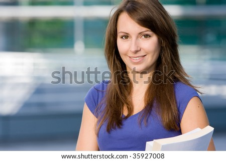 Pretty attractive caucasian white girl standing outside modern college school with books - stock photo