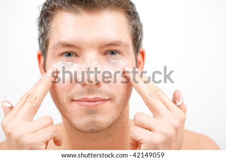 Pretty attractive man beautify applying rejuvenate cream on face for better male macho appearence - stock photo